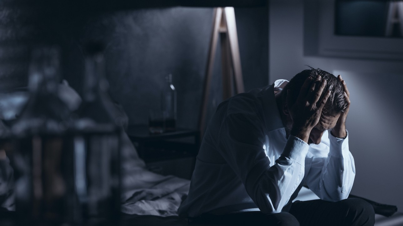 Depressed man with alcohol problem. Workaholic in the dark