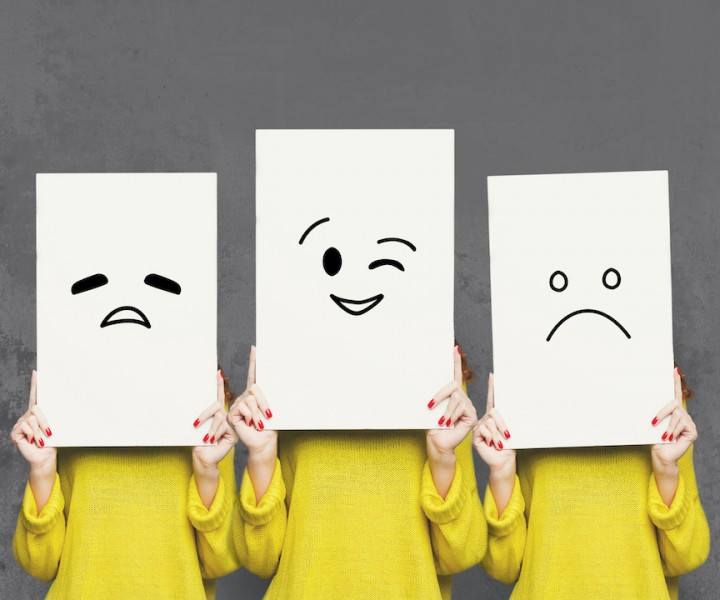 Emotions set. Girl hiding face behind signboard with drawn smileys. Collage of tired, winking and sad emoticons.